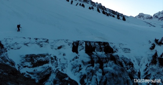 La nieve en la aproximación está muy dura y al contornear el barranco de Ip nos calzamos los crampones...