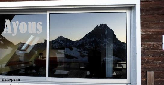 Reflejo de la Jean Pierre en la cristalera panorámica del refugio